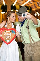 Young couple taking self portrait at Oktoberfest, Munich, Germany