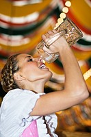 Young woman drinking beer in beer tent at Oktoberfest, Munich, Germany