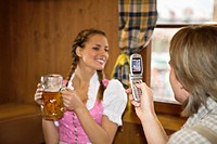 Young man taking photo of girl with cell phone at Oktoberfest, Munich, Germany
