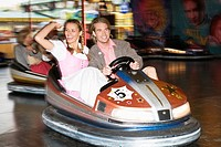 Young couple riding in bumper car at Oktoberfest beer festival, Munich, Germany