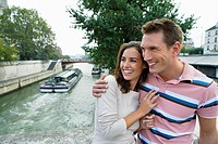 Young couple by river Seine with tourist boat in background, Paris, France