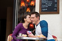 Young couple outside street side cafe, woman kissing man, Paris, France