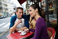 Young couple sitting drinking coffee outside street side cafe, Paris, France