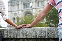 Detail of couple holding hands in front of Notre Dame Cathedral, Paris, France