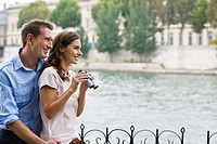Young couple embracing by river Seine, woman holding binoculars, Paris, France