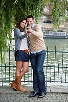 Young couple by river Seine, man taking picture with camera phone, Paris, France