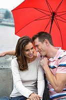 Couple sitting on Pont Neuf bridge under red umbrella Paris, France