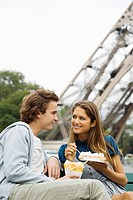 Young couple eating fast_food with Eiffel tower in background, Paris, France