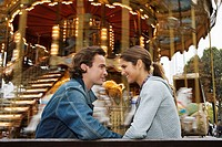 Young couple sitting on bench with Carousel in background, Paris, France