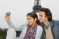 Young couple, woman taking photo with digital camera, Eiffel tower in background