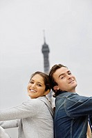 Young couple sitting back to back with Eiffel tower in background, Paris, France