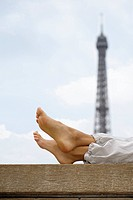 Close up of woman's legs with Eiffel tower in background, Paris, France