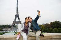 Young couple sitting on wall, man taking photo, Eiffel tower in background