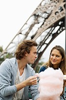 Young couple in front of Eiffel tower man eating cotton candy, Paris, France