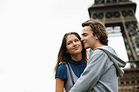 Young couple kissing with Eiffel tower in background, Paris, France (thumbnail)