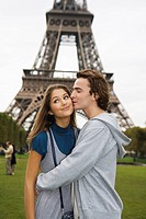 Young couple kissing with Eiffel tower in background, Paris, France