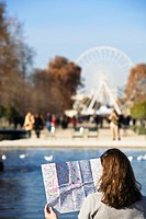 Woman looking at map with Place de la Concorde, big wheel in background, Paris