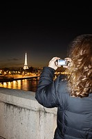 Woman taking picture of Eiffel Tower at night, Paris, France