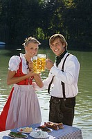 Young couple in traditional Bavarian outfit, having meal in beer garden Munich (thumbnail)