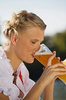 Young woman in traditional Bavarian dress, drinking beer, side profile
