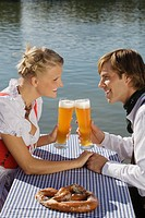 Young couple in traditional Bavarian outfit, sitting in beer garden, Munich