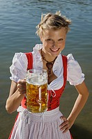 Young woman in traditional Bavarian dress, holding litre glass of beer