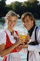 Young couple in traditional Bavarian outfit, in beer garden, Munich, Germany