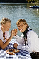 Young couple in traditional Bavarian outfit, eating Pretzel, Munich (thumbnail)