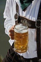 Detail of man in traditional Bavarian, Lederhosen, holding litre glass of beer