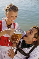 Young couple in traditional Bavarian outfit, woman giving man drink of beer