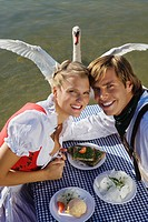 Young couple in traditional Bavarian outfit, with swan in background, Munich