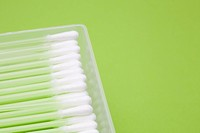 Box of cotton buds on green background