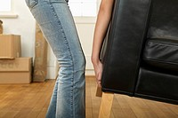 Young woman moving sofa