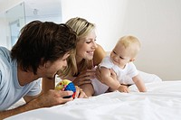 Young parents playing with baby 6_12 months on bed, baby looking at toy