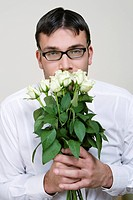 Stupid looking young man with bunch of flowers