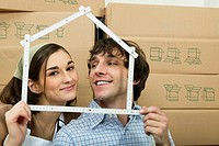 Couple holding ruler in shape of house