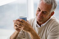 Mature man holding cup of coffee