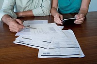 Mature couple looking at bills, using calculator, detail of hands