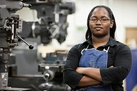African woman standing in machine tooling plant