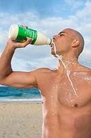 Mixed race man drinking and spilling protein shake on beach