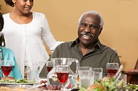 African man laughing at dinner table