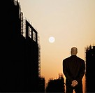 Mixed race businessman looking at sun setting in sky