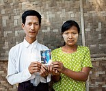 Asian couple holding photograph