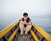 Asian man on boat taking photograph with cell phone