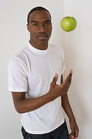 African man tossing apple