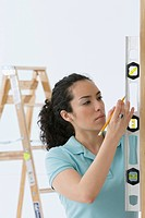 Hispanic woman using spirit level tool