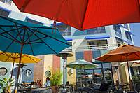 USA, California, Alameda County, Oakland, Jack London Square, outdoor restaurant with umbrellas, diners, hotel, overlooking Oakland Inner Harbor water...