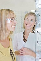 Woman trying on glasses in optometrist's shop