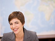 Businesswoman smiling in front of map