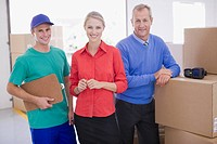 Business people and delivery man in warehouse
